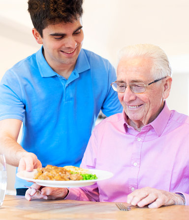 elder man being served with food by a home care assistant