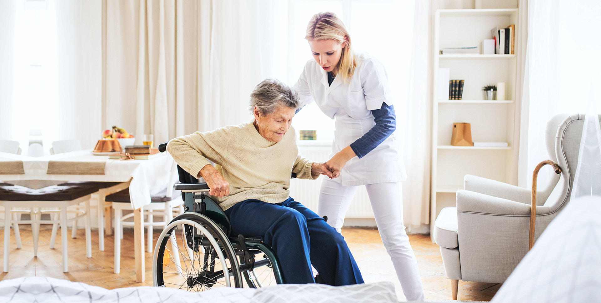 elder woman on a wheelchair assisted by caregiver in standing up