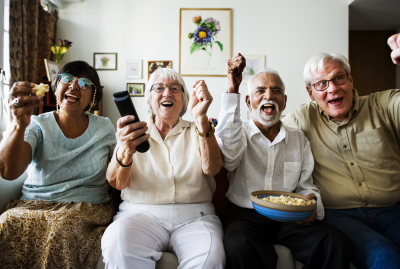 group of cheerful elderly sitting and watching TV together