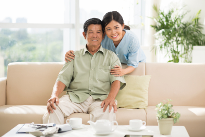 smiling caregiver hugging elder man