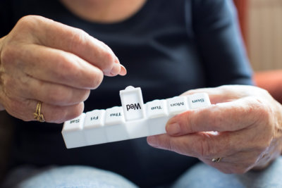 elder woman taking medication from pill box concept