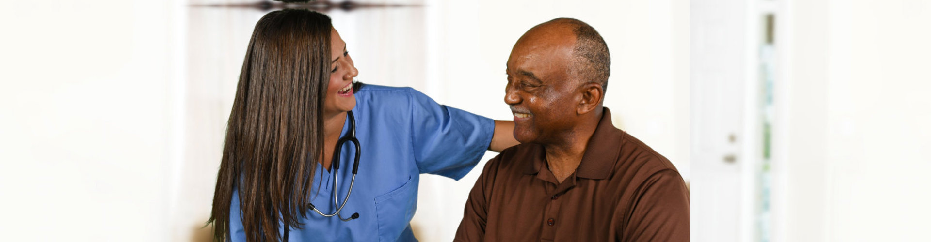 elder man with caregiver looking at each other