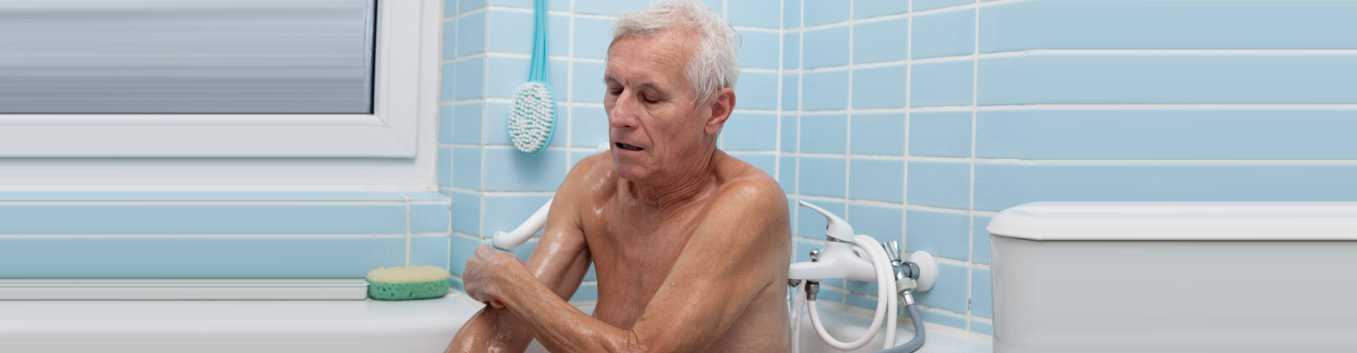 elder man washing his body with soap sponge in bath