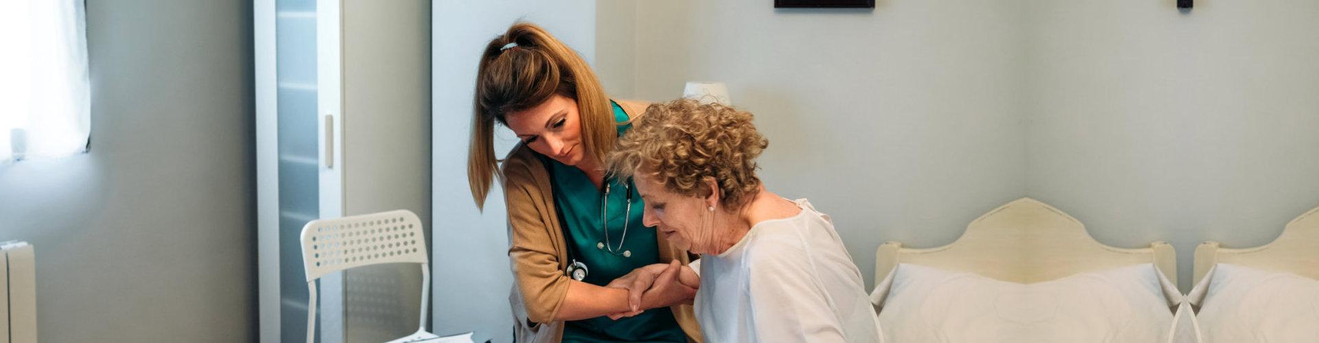 caregiver assisting elder woman on standing up